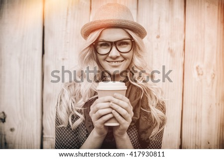 Cheerful fashionable blonde holding coffee outdoors on wooden background - stock photo