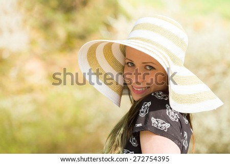 Cheerful fashionable woman in stylish hat and frock posing outdoor. Happy brunette girl with long hair in warm spring day - stock photo