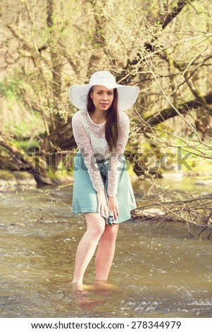 Cheerful fashionable woman in stylish hat and frock posing outdoor in creek. Happy brunette girl with long hair in warm spring day. Vinatge color tone. - stock photo