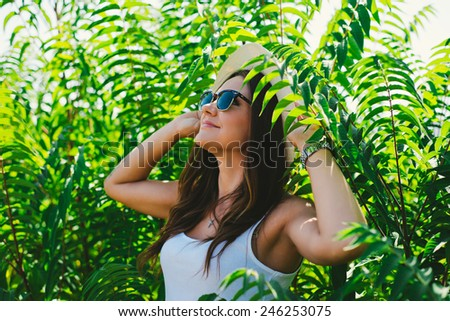 Cheerful fashionable woman in stylish hat and jeans shorts posing. Hipster style.  - stock photo