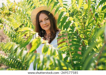 Cheerful fashionable woman in stylish hat and jeans shorts posing. Hipster style. girl with long hair poses in warm spring day - stock photo