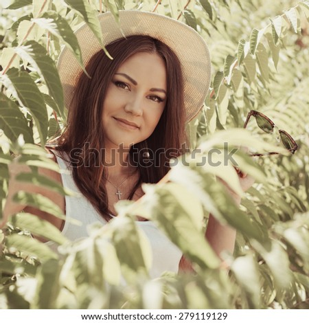 Cheerful fashionable woman in stylish hat and jeans shorts posing. Hipster style. girl with long hair poses in warm spring day. Photo with instagram style filters - stock photo