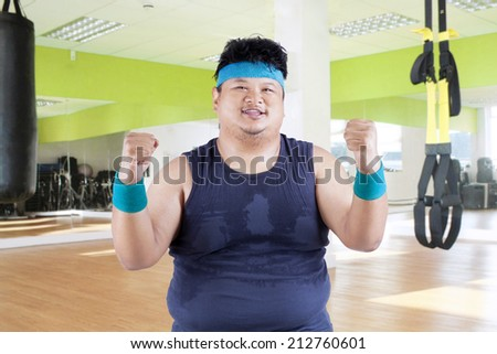 Cheerful fat man in fitness center after workout - stock photo