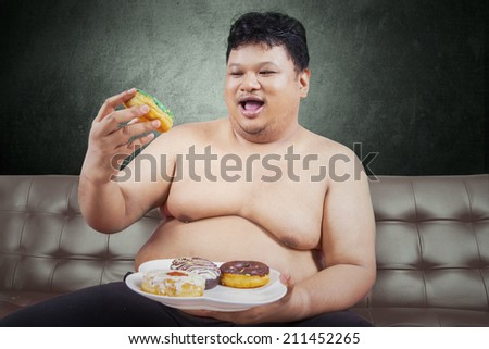 Cheerful fat man looking at donuts while sitting on the sofa at home - stock photo