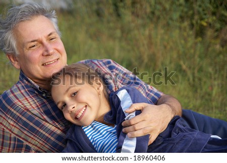 Cheerful father and daughter talking in park - stock photo