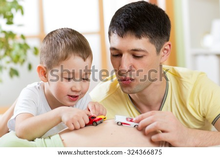 Cheerful father and his son have a fun playing with tiny toys car on pregnant wife belly.  - stock photo