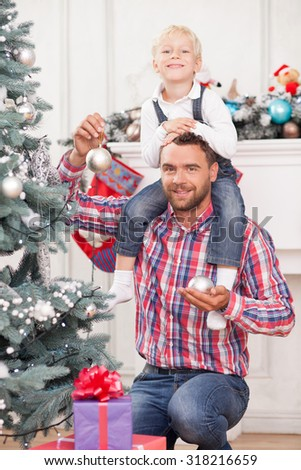 Cheerful father and son are decorating Christmas tree. They are looking at the camera and smiling. The parent is holding boy on his shoulders and spheres in hands. The boy is sitting with joy - stock photo