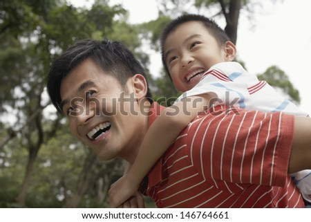 Cheerful father and son enjoying piggyback ride in park - stock photo
