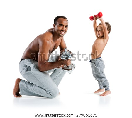 Cheerful father and son exercising with dumbbells and smiling / photo set of sporty muscular Hispanic shirtless fitness man with his son over white background - stock photo