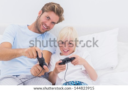 Cheerful father and son playing video games in bed - stock photo