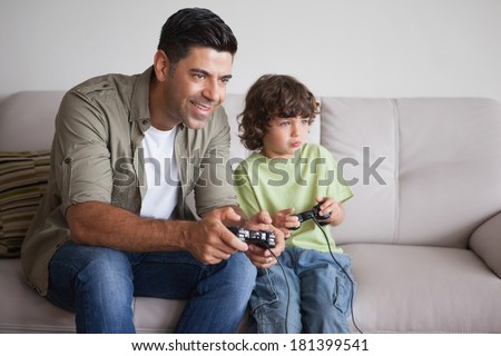 Cheerful father and son playing video games in the living room at home - stock photo