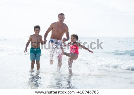Cheerful father enjoying with children in shallow water at beach - stock photo