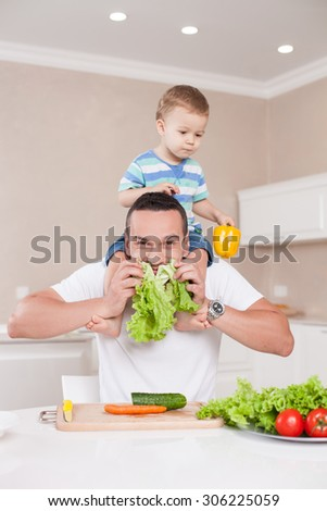 Cheerful father is sitting at the table in kitchen and raising leaves of lettuce to his beard with fun. He is holding his son on shoulders and smiling. The boy is looking at vegetables with appetite