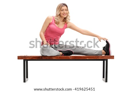 Cheerful female athlete stretching her leg seated on a bench isolated on white background