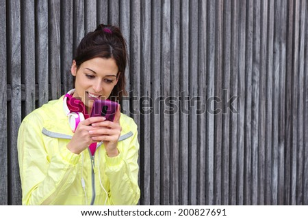 Cheerful female athlete texting message or email on smartphone on a urban workout break. Sporty woman looking her cellphone. - stock photo