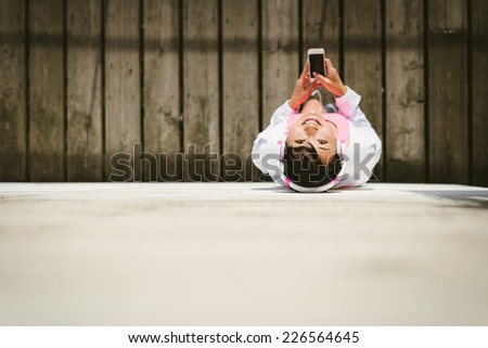 Cheerful female athlete with smartphone and headphones view from above. Asian sporty woman taking a work out rest. - stock photo