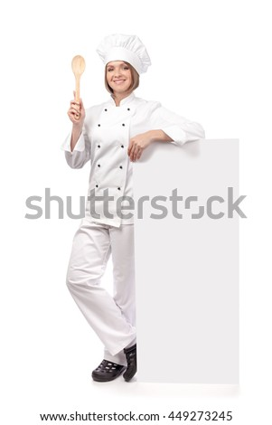 cheerful female chef, cook or baker holding spoon and standing next to the banner with empty copy space for you text isolated on white background. advertisement blank board. your text here - stock photo