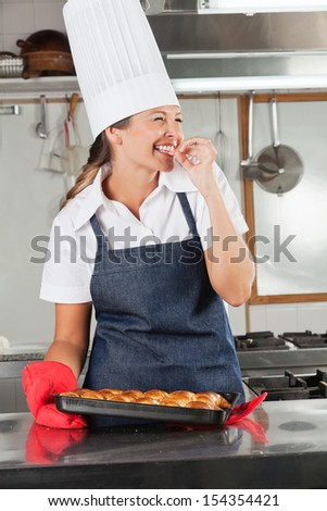 Cheerful female chef tasting baked bread in commercial kitchen - stock photo