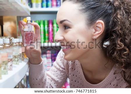 Cheerful female customer buying perfume in fragrance section of supermarket