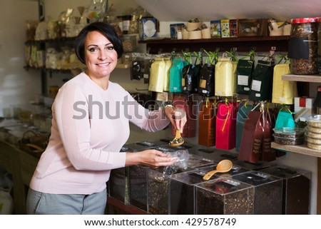 Cheerful female customer selecting various tea kinds in the store with ecological goods - stock photo