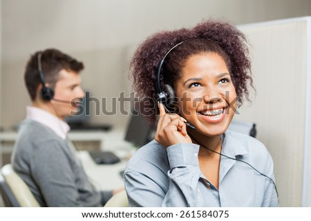 Cheerful female customer service representative with male colleague in office