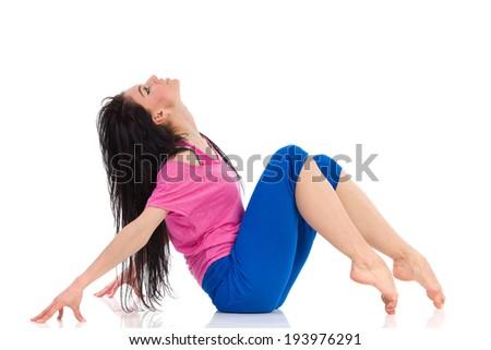 Cheerful female dancer posing sitting on the floor. Full length studio shot isolated on white. - stock photo