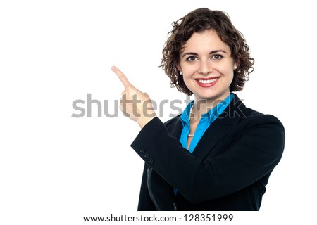 Cheerful female entrepreneur pointing towards copy space area. - stock photo