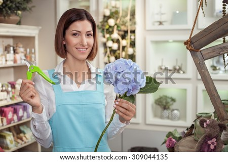 Cheerful female florist is standing in her workshop and smiling. She is holding a plant and scissors and showing it to the camera. The woman is preparing to cut its length - stock photo