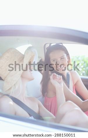Cheerful female friends enjoying road trip in car - stock photo