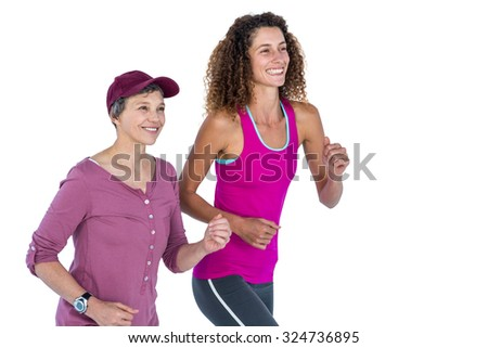 Cheerful female friends jogging against white background - stock photo