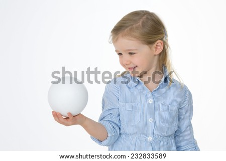 cheerful female kid looks at her new toy - stock photo
