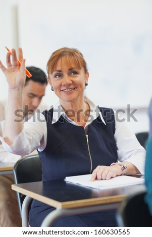Cheerful female mature student raising her hand while sitting in classroom - stock photo