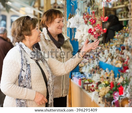 Cheerful female pensioners buying X-mas decorations at fair. Focus on left person  - stock photo