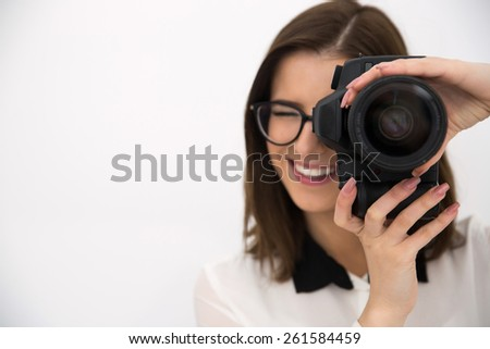 Cheerful female photographer with camera over gray background - stock photo