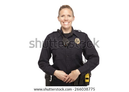 Cheerful female police officer standing against white background - stock photo