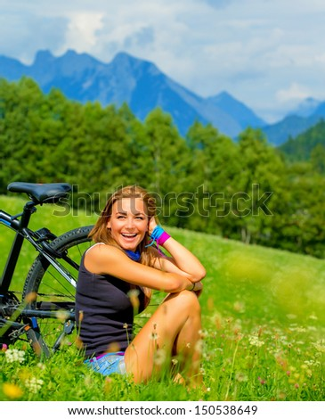 Cheerful female resting on green field after riding on bicycle, Alps mountains background, biking traveling along Austria, summer vacation concept  - stock photo