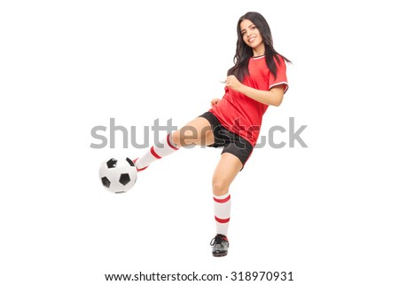 Cheerful female soccer player shooting a ball and looking at the camera isolated on white background - stock photo