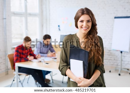 Cheerful female student standing in classroom
