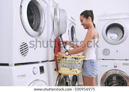 Cheerful female student taking clean clothes out of washing machine