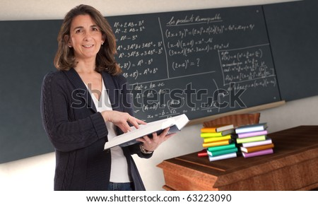 Cheerful female teacher holding a book in a maths classroom - stock photo