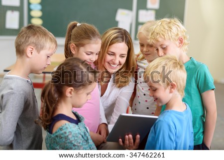 Cheerful Female Teacher with her Young Students Watching a Video on a Tablet Computer Together Inside the Classroom. - stock photo