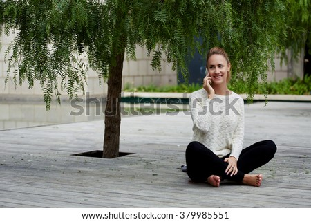 Cheerful female teenager phoning to friend with cell telephone during recreation time on wooden pier, charming woman with beautiful smile talking on mobile phone while sitting outdoors in spring day - stock photo