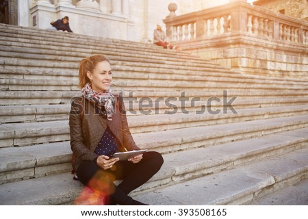 Cheerful female tourist is smiling for someone, while is sitting with portable touch pad in hands outdoors on a stairs. Young happy woman student is holding digital tablet, while is resting on campus - stock photo