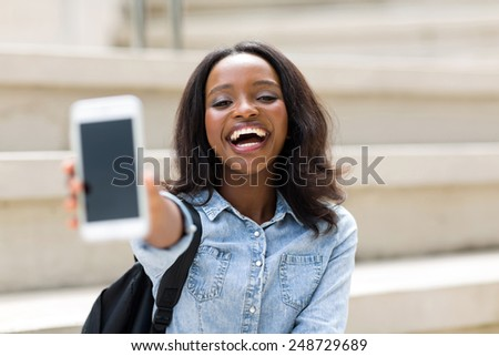 cheerful female university student showing smart phone - stock photo