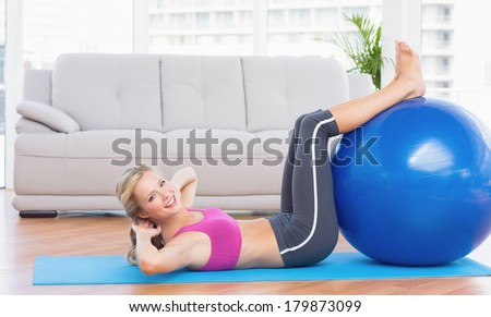 Cheerful fit blonde doing sit ups with exercise ball at home in the living room - stock photo
