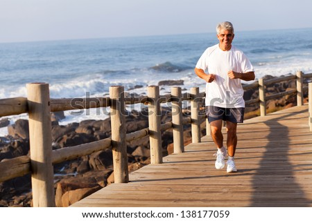 cheerful fit senior man running at the beach in the morning - stock photo