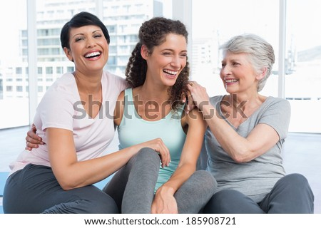 Cheerful fit women sitting in the yoga class - stock photo