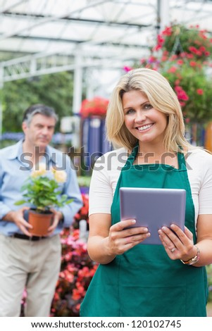 Cheerful florist holding a tablet pc in garden center with customer standing behing holding flower pot - stock photo