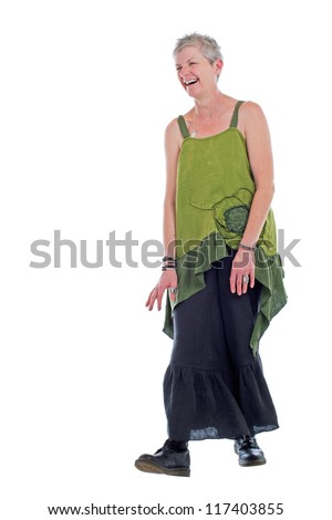 Cheerful friendly older woman stands in loose flowing long green linen two piece dress with ruffle. She has short gray hair. Isolated on white background, vertical.