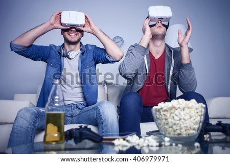 Cheerful friends are watching modern headset - stock photo